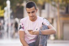 Ung tillfällig man som går och läser meddelanden på den smarta phonen royaltyfri foto
