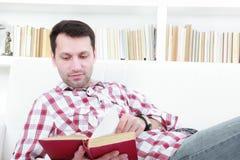 Ung tillfällig man som läser en bok som kopplar av på soffan royaltyfri fotografi