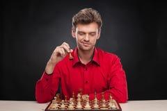 Ung tillfällig man som sitter över schack Arkivfoto