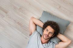 Ung tänkande man som ligger på golv Royaltyfri Foto