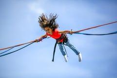 Ung tonårig flicka i bungeebanhoppningtrampolin Arkivbilder