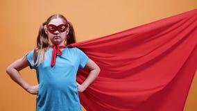 Ung tonårig flicka med en superherokappa som blåsas av vind arkivfilmer
