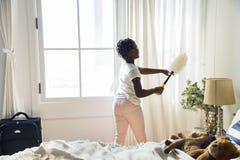 Ung tonårig flicka som upp gör ren sovrummet royaltyfria foton