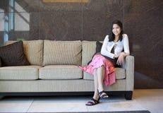 Ung tonårig flicka som vilar på en elegant soffa royaltyfria foton