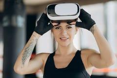 Ung tonårig gamer som bär ökade verklighetexponeringsglas som står i boxningslagställning som spelar den modiga mobila appen för  royaltyfri fotografi