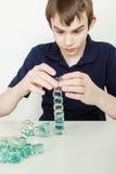 Ung tonårig pojke som staplar Glass kvarter in i torn Arkivfoto