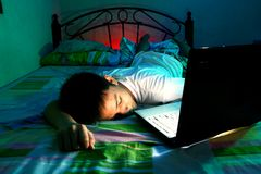 Ung tonårig sova framdel av en bärbar datordator och på en säng Arkivfoton