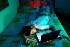 Ung tonårig sova framdel av en bärbar datordator och på en säng Arkivbild