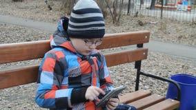 Ung tonåring som spelar leken på smartphonen på bänken utanför arkivfilmer