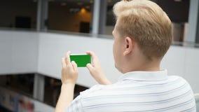 Ung tonåring som spelar leken på smartphonen i kafé Ung lycklig man som spelar lekar på smartphonen Smartphone vänder på på lager videofilmer
