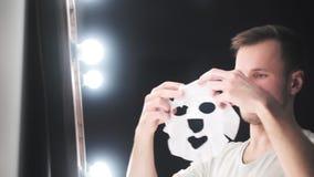 Ung tonåringpojke för skönhet som applicerar den kosmetiska framsidamaskeringen och beundrar sig i spegeln arkivfilmer