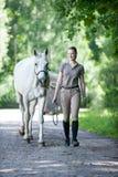 Ung tonårs- blondy flicka som leder hennes favorit- vita häst royaltyfria bilder
