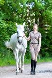 Ung tonårs- blondy flicka som leder hennes favorit- vita häst royaltyfri bild