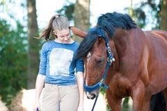 Ung tonårs- flicka nära hennes favorit- kastanjebruna häst royaltyfria foton