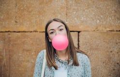 Ung tonårs- flicka som blåser rosa bubbelgum Fotografering för Bildbyråer