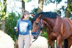 Ung tonårs- flicka som nästan står hennes favorit- kastanjebruna häst fotografering för bildbyråer