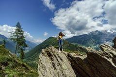 Ung tonårs- flicka som poserar på den stora stenen i fjällängar royaltyfri fotografi