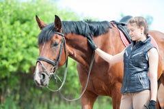 Ung tonårs- flicka som ser ömt hennes favorit- röda häst royaltyfria foton