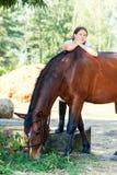 Ung tonårs- gladlynt flickaryttare som kramar hennes favorit- ches royaltyfri bild