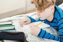 Ung tonårs- pojke som gör hans läxa Arkivfoton