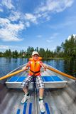 Ung tonårs- pojke som ror en roddbåt på en sjö med blå sommarhimmel i bakgrunden royaltyfri bild