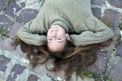 Ung trendig flicka som ligger på trottoaren Arkivfoto