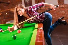 Ung trendig flicka som spelar billiard Fotografering för Bildbyråer