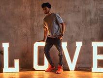 Ung trendig indisk grabb som poserar med omfångsrika bokstäver med belysning arkivfoto