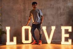 Ung trendig indisk grabb som poserar med omfångsrika bokstäver med belysning royaltyfri bild