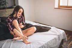 Ung trevlig kvinna som förbereder sig och talar med hennes flickvän på telefonen Royaltyfria Foton