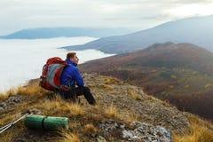 Ung turist- fotvandrare med ryggsäcken som placerar och kopplar av på överkanten av berget och ser härlig gul höst Arkivfoton