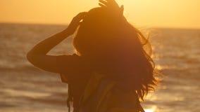 Ung turist- kvinna som binder hästsvansen på stranden nära havet på solnedgången Den härliga flickan pressar hennes hår på havkus arkivfilmer