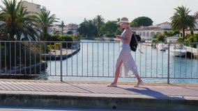 Ung turist- kvinna som går på bron över kanalen Området Empuriabrava, Spanien Använd smartphones Begrepp - arkivfilmer