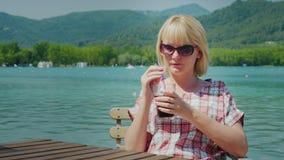 Ung turist- kvinna som kopplar av i ett härligt läge vid sjön och bergen i Spanien Drinkar gör till kok från ett exponeringsglas  arkivfilmer
