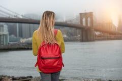 Ung turist- kvinnaresande i nya New York City med den röda ryggsäcken och se till den Brooklyn bron Royaltyfri Fotografi
