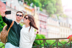 Ung turist- parresande på ferier, i Europa att le som är lyckligt Caucasian familj med stadsöversikten i sökande av Royaltyfria Bilder