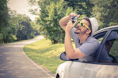 Ung turist som tar foto från bilen, genom att använda den retro kameran Royaltyfria Bilder
