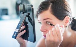 Ung underbar kvinna som applicerar hennes härliga makeup i en spegel Fotografering för Bildbyråer