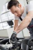 Ung underhållstekniker som reparerar bilen i billager Royaltyfri Foto
