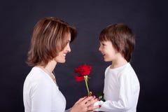 Ung unge som ger den ursnygga röda rosen till hans mamma Royaltyfri Fotografi