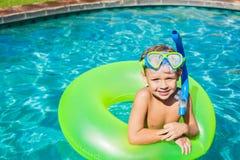 Ung unge som har gyckel i simbassängen Royaltyfri Foto