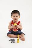 Ung unge som spelar med färgrika leksaker Arkivbilder