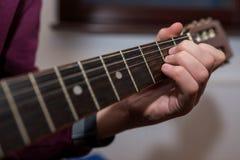 Ung unidentifiable musiker som spelar på gitarren arkivfoton
