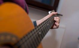 Ung unidentifiable musiker som spelar på gitarren royaltyfri bild