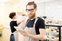 Ung uppassare för allvarlig hipster i kafé royaltyfria foton