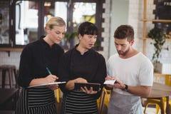 Ung uppassare och servitris som diskuterar över den digitala minnestavlan arkivfoto