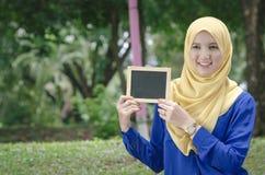 Ung upphetsad kvinna som rymmer den tomma tomma svart tavlan för text Arkivfoto