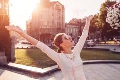 Ung upphetsad kvinna som utomhus känner sig fri Lycklig flicka som lyfter armar och har gyckel royaltyfria bilder