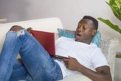 Ung upphetsad och förvånad ung svart afrikansk amerikanman i nätverkande för misstro- och chockframsidauttryck med bärbara datorn royaltyfria foton