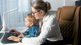 Ung upptagen kvinna som i regeringsställning arbetar med hennes litet barnpojke Fotografering för Bildbyråer